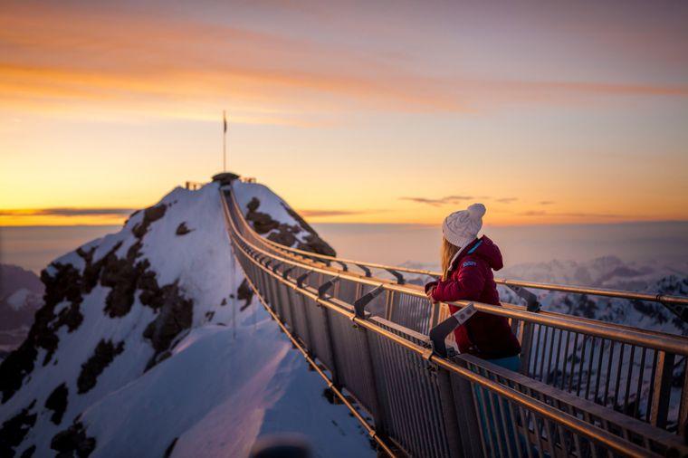 Echter Nervenkitzel: Das vereiste Geländer des Peak Walk glitzert in der Abendsonne, während die Hängebrücke im Wind schaukelt.