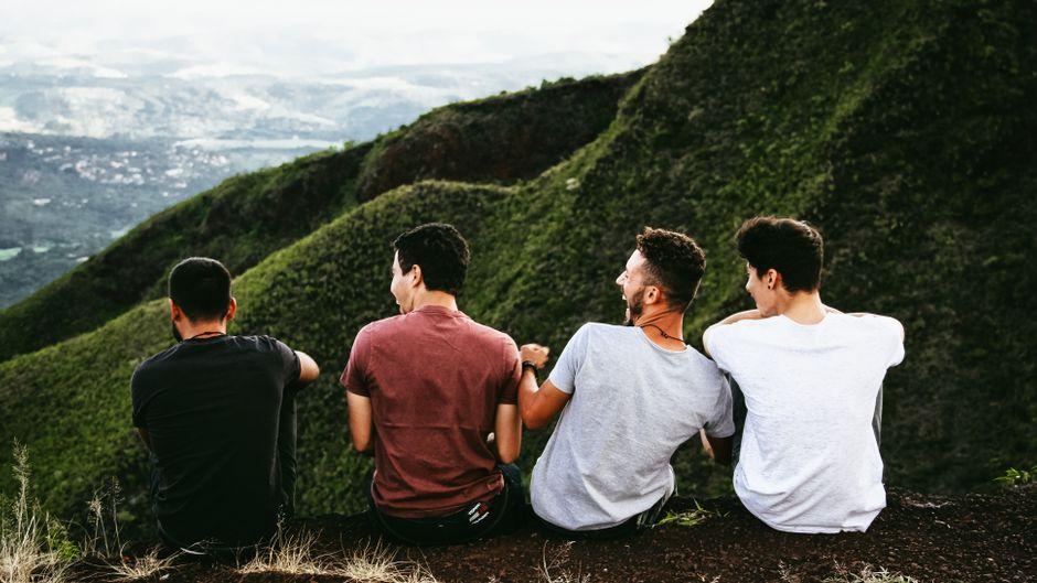 Freunde sitzen in der Natur und lachen.