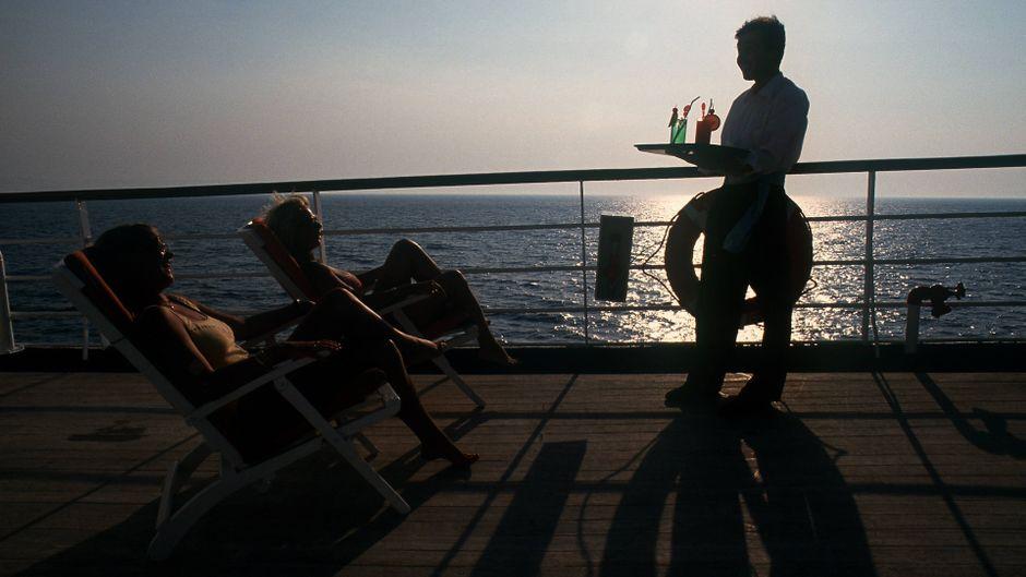 Ein Kellner serviert auf dem Sonnendeck eines Kreuzfahrtschiffs Getränke.