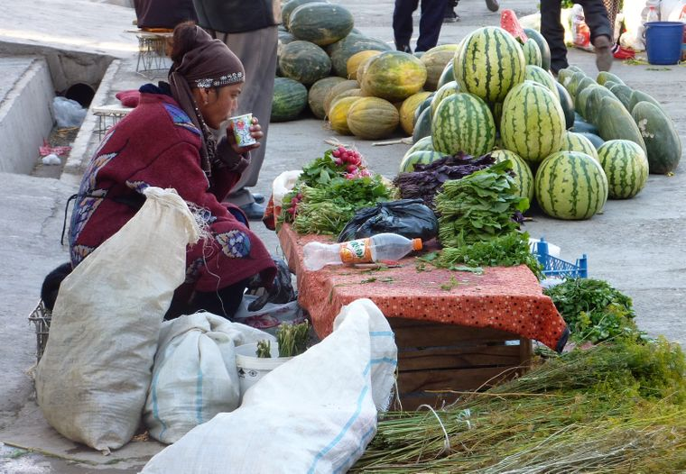 Eine Bäuerin verkauft auf dem Markt in Samarkand frisches Gemüse