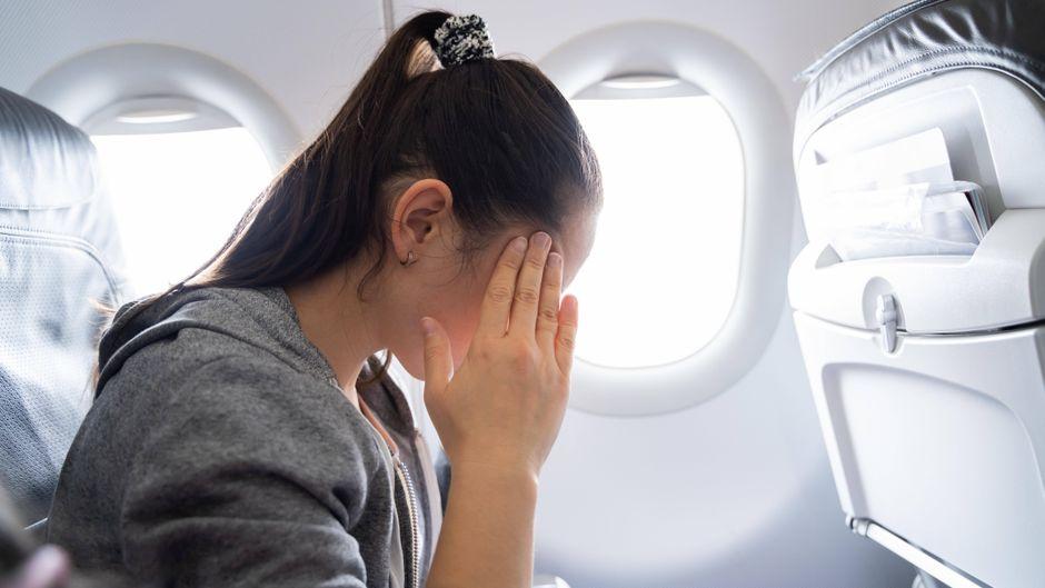 Eine Frau, die an Reiseübelkeit leidet, sitzt im Flugzeug.