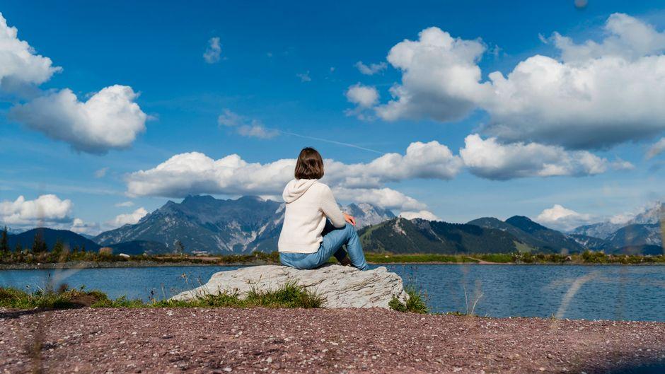 Eine Frau sitzt auf einem Berg in Österreich – Wandern und Urlaub in dem Land sollen bald wieder möglich werden.