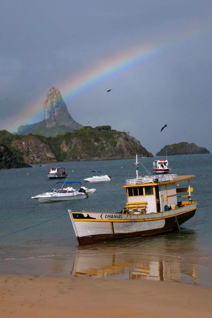 Ein Schnappschuss: Über der Insel breitet sich ein Regenbogen aus, während einige Boote am Strand anlegen.