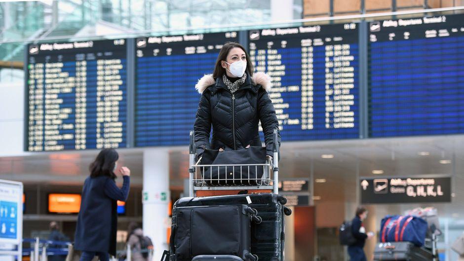 Frau mit Maske am Flughafen München – ist die Fahrt zum Airport trotz Ausgangssperre möglich?