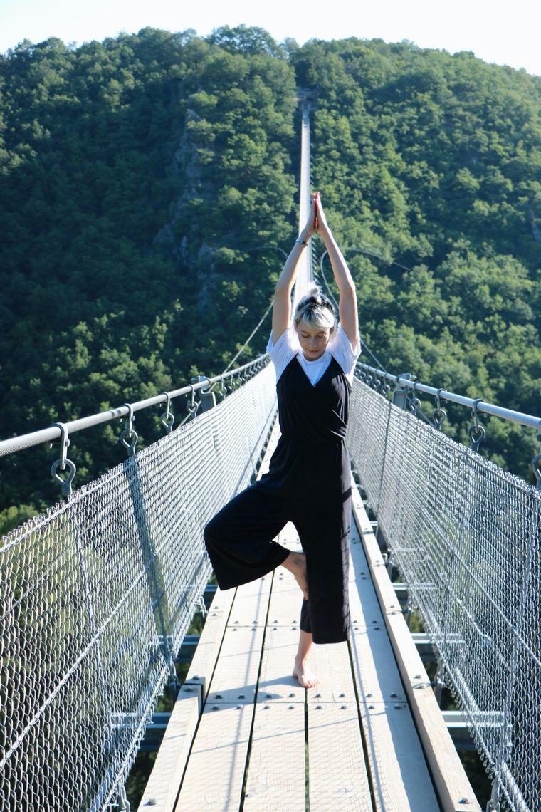 Eine Frau steht in der Yoga-Postion Baum auf der Geierlay Hängebrücke in Rheinland-Pfalz.