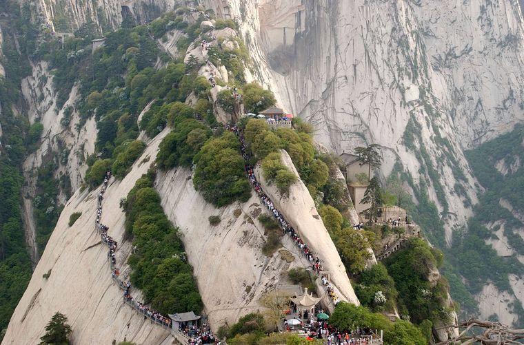 Stau am Mount Hua – Touristen wollen den Gipfel erklimmen, teilweise auf morschen Holzplatten am Abgrund entlang.