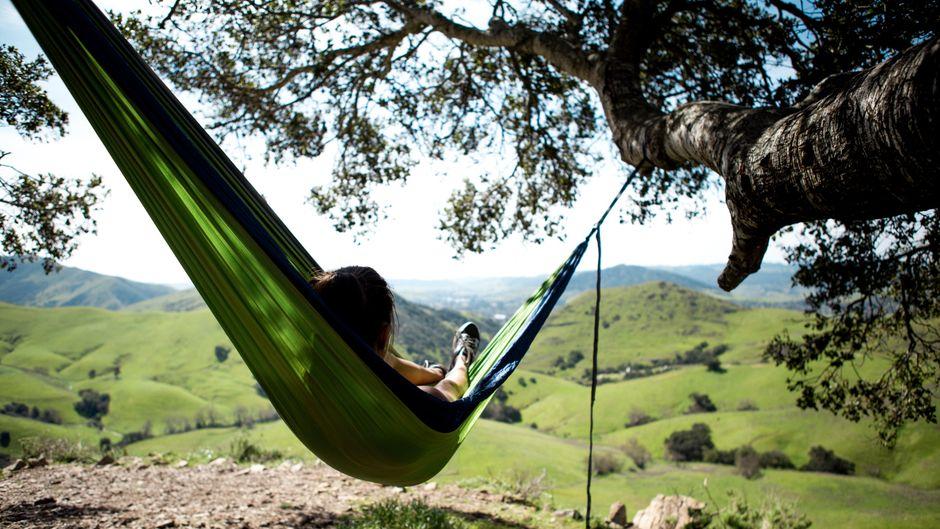 Eine Frau liegt in einer Hängematte inmitten einer hügeligen Landschaft.