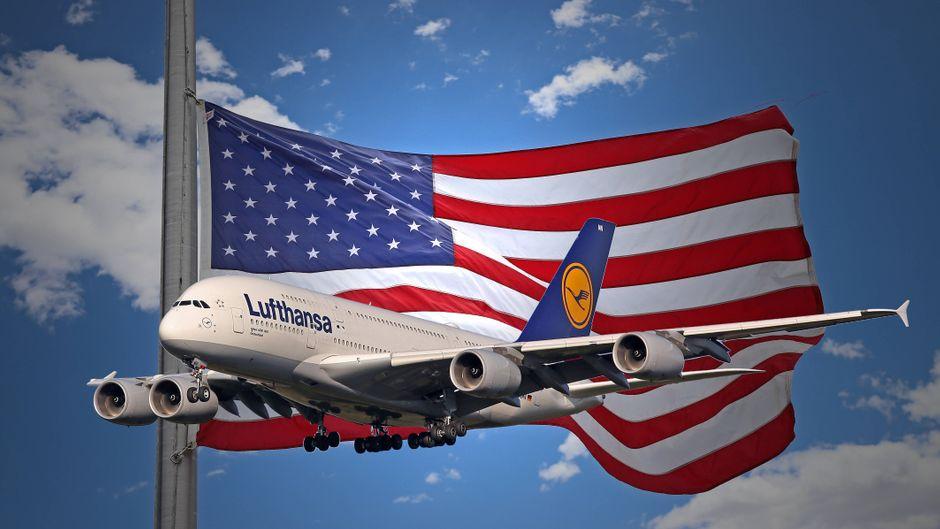 Lufthansa-Flugzeug vor einer USA-Flagge: Die USA stoppen 30 Tage lang Einreisen aus Europa.