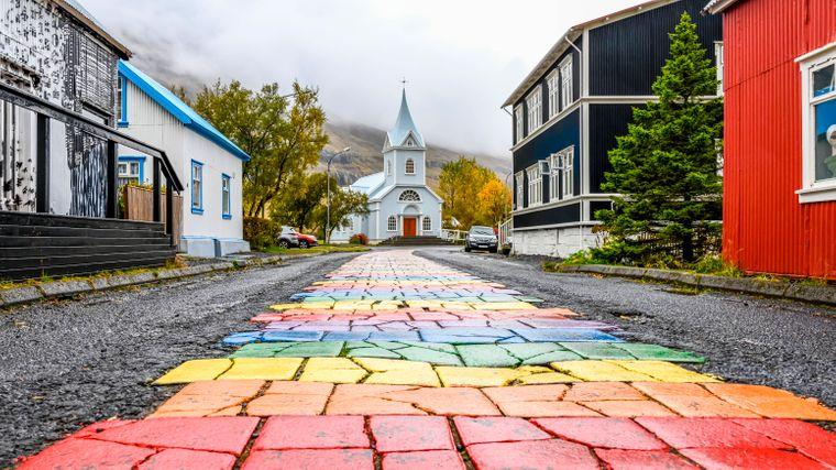 Ein echter Hingucker sind der Regenbogenweg und die weiße Kirche in Seydisfjördur.