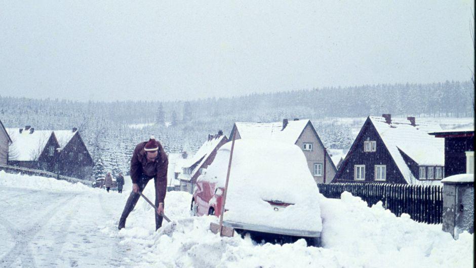 Mühsam schaufelt der Besitzer sein Auto vom Schnee frei.